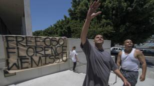 Un homme fait signe à des membres de sa famille qui ont été arrêtés lors d'une précédente opération de la police à Los Angeles, le 14 juillet 2019.