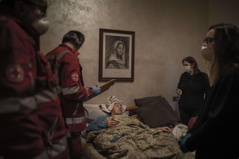 Claudio Travelli  se repose dans son lit après avoir été examiné par les volontaires de l'IRC, à Pregunta, en Italie, le 15 mars 2020.