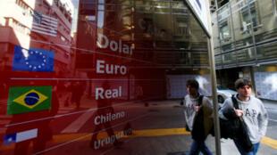 Archivo-Un hombre pasa junto a un tablero electrónico que muestra los tipos de cambio de divisas, en Buenos Aires, Argentina, el 20 de agosto de 2019.