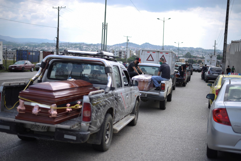 Des véhicules transportant des cercueils attendent devant un cimetière de Guayaquil, en Équateur, le 2 avril 2020.