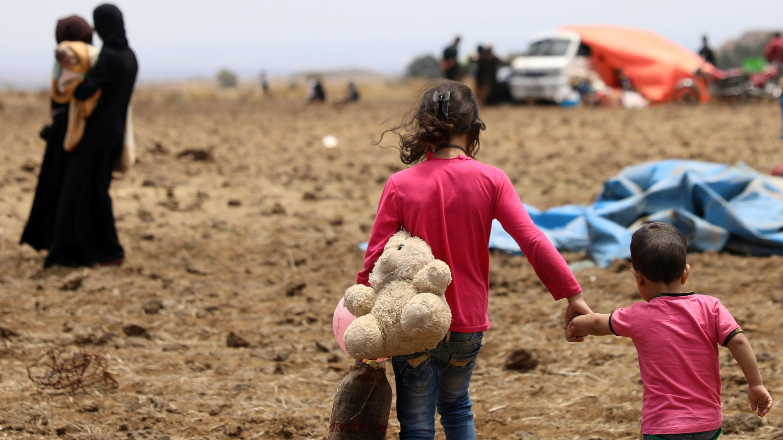 Una niña internamente desplazada de la provincia de Deraa lleva un juguete de peluche y sostiene la mano de un niño cerca de los Altos del Golán ocupados por Israel en Quneitra, Siria. 29 de junio de 2018.