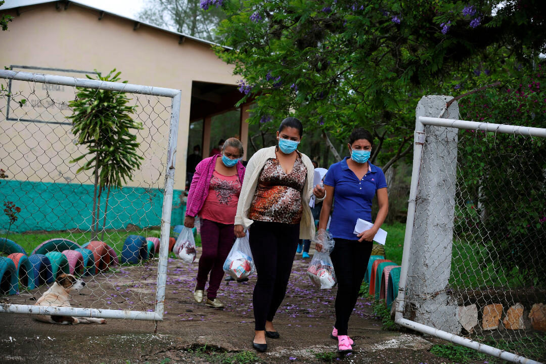 Fotografía fechada el 5 de junio de 2020 que muestra a madres de familia mientras abandonan una reunión escolar donde recibieron una ración de alimento, en la aldea de Zuntule, al oriente de Tegucigalpa (Honduras).