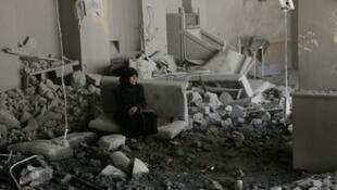 امرأة تجلس داخل منزل مهدم في حي طريق الباب في حلب