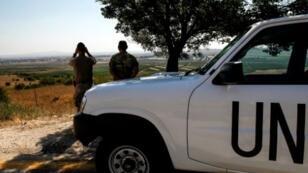 عنصران من قوة الأمم المتحدة يراقبان الأراضي السورية من القسم الذي تحتله إسرائيل في الجولان في 22 تموز/يوليو 2018