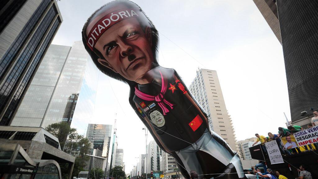 Brasileños sostienen un muñeco gigante burlándose del gobernador de Sao Paulo, Joao Doria, durante una manifestación en el Día del Trabajo contra el aislamiento social y a favor de una intervención militar, este viernes en la Avenida Paulista de Sao Paulo, Brasil, el 1 de mayo de 2020.