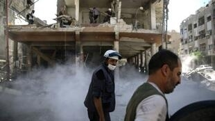 """متطوعان من منظمة """"الخوذ البيضاء"""" يقومان بمهمة إنقاذ في دوما شرق دمشق في 5 أكتوبر 2016"""
