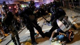 Un policía detiene a un manifestante durante las protestas del domingo 28 de julio.