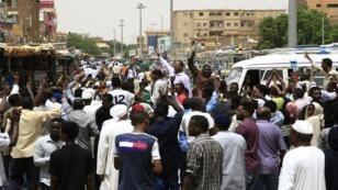 المتظاهرون السودانيون يرددون شعارات أثناء مظاهرة حاشدة ضد المجلس العسكري، شمال الخرطوم، 30 يونيو/حزيران 2019