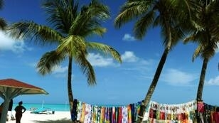 In this file photo, a vendor displays colorful clothing on a beach in St. John's, Antigua and Barbuda, where voters on November 6, 2018 will decide whether to keep a London-based body as their final appeals court or embrace one closer to home