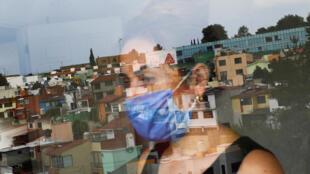 Mónica Samudio, de 46 años, cuyo esposo Jorge García, de 51 años, murió a causa de la enfermedad por coronavirus (COVID-19), se refleja en la ventana mientras mira hacia su nuevo departamento, en la Ciudad de México, México, 29 de abril de 2020. Samudio dijo que ella se mudó de su hogar anterior después de sentirse discriminada cuando ella y su esposo contrajeron la enfermedad. Fotografía tomada el 29 de abril de 2020.