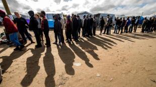 Des migrants patientent pour obtenir de la nourriture dans la New Jungle de Calais, le 19 septembre 2015.