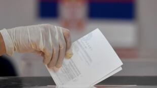 Una mujer con guantes protectores vota en una mesa electoral en Belgrado el 21 de junio de 2020 durante las primeras elecciones nacionales de Europa desde la pandemia de coronavirus.