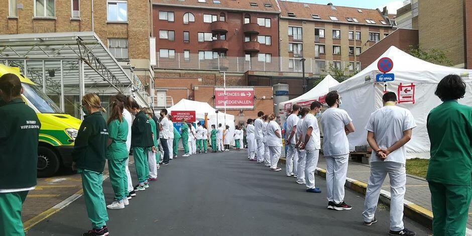 Des personnels soignants de l'hôpital Saint-Pierre de Bruxelles tournent le dos au cortège officiel lors de la venue de la Première ministre belge, Sophie Wilmès, le 16 mai 2020.