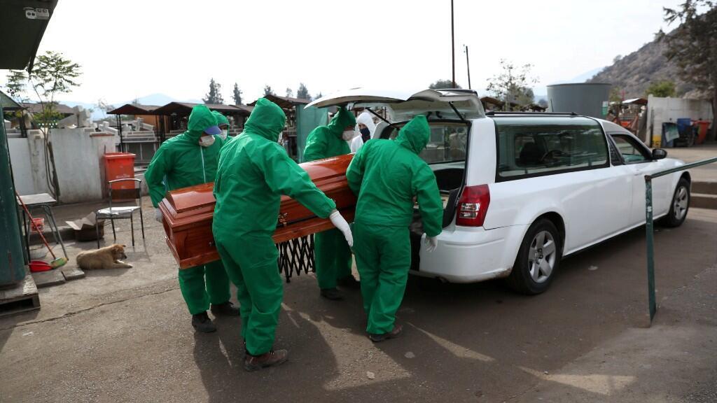 Los trabajadores del cementerio llevan el ataúd de José, de 68 años, quien murió de la enfermedad por coronavirus, durante su funeral en el área de Colina, Santiago, Chile, el 19 de junio de 2020.