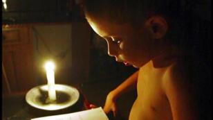En la foto tomada en La Habana hace 15 anos cuando hubo un racha de apagones, el joven Raidel Rodríguez se ve estudiando a la luz de una vela. Hoy Raidel tiende 23 años vive en Miami y curiosamente, trabaja en una compañía eléctrica estadounidense. José Goitia.