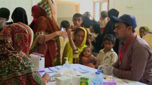 Funcionarios del Programa de Control del Sida en la provincia de Sindh, Pakistán, realizan análisis de sangre para el VIH en menores.