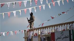 Un combatiente rebelde sirio respaldado por Turquía monta guardia durante una manifestación en apoyo de la operación de la Rama de Olivo del ejército turco en la ciudad siria de Surán el 1 de febrero de 2018.