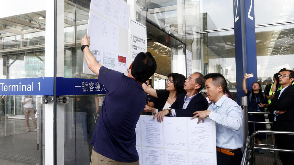 Unos funcionarios publican una orden judicial para impedir que la gente obstruya las operaciones aeroportuarias en la entrada de la Terminal 1 del Aeropuerto de Hong Kong, este 14 de agosto.