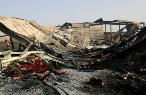 يمنيون يتفقدون الأضرار في مصنع تعرض لقصف جوي في مدينة الحديدة في 27 تموز/يوليو 2018
