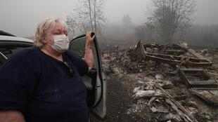 Margi Wyatt stands in front of her incinerated mobile home