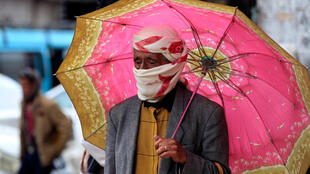 A Yemeni man wearing a scarf over his face as a protective measure against the novel coronavirus walks in a market in the Yemeni capital Sanaa where the Huthi rebels on Tuesday announced the first death from coronavirus