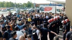 عناصر من الأمن الماليزي يحرسون مطار السلطان عبدالعزيز شاه حيث احتشد محتجون غاضبون وإعلاميون في 12 أيار/مايو 2018
