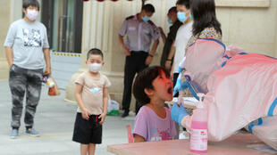 A health worker carries out a Covid-19 coronavirus test on a child at a makeshift testing center in Dalian, in China's northeast Liaoning province on July 27, 2020.