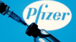 A vial and sryinge are seen in front of a displayed Pfizer logo in this illustration taken January 11, 2021.