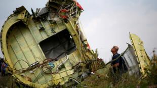 Un investigador en accidentes aéreos de Malasia, inspecciona el sitio del accidente del vuelo MH17 de Malaysia Airlines , en la región de Donetsk. Julio 22 de 2014.