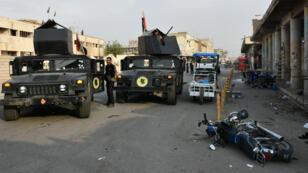 Des agents des forces de sécurité irakiennes examinent le lieu d'une des deux attaques-suicides à Kirkouk, le 5 novembre 2017.