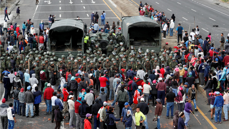 Un grupo de manifestantes rodea a los militares mientras bloquean una carretera en medio de las protestas contra las recientes medidas del Gobierno, en Lasso, Ecuador, el 6 de octubre de 2019.