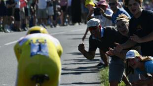 Espectadores vitorean mientras el esloveno Tadej Pogacar, del equipo de Emiratos Árabes Unidos avanza durante la vigésima etapa de la 108a edición de la carrera ciclista del Tour de Francia, una contrarreloj de 30 km entre Libourne y Saint-Emilion, el 17 de julio de 2021.