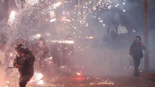 Lebanese riot police react to fireworks thrown by supporters of Lebanon's Shiite Hezbollah and Amal groups during clashes on December 14, 2019 in central Beirut.