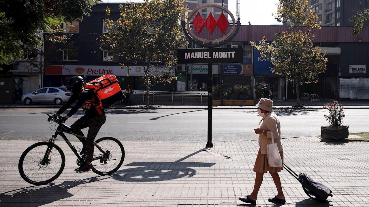 Una mujer mayor caminas con un carro de la compras junto a un repartidor en una calle casi vacía en la ciudad de Santiago. 18 de abril de 2020.