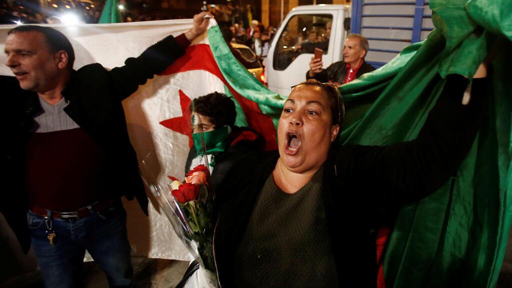 Las personas portan una bandera nacional mientras celebran en las calles después de que el presidente de Argelia, Abdelaziz Bouteflika, presentó su renuncia en Argel, Argelia, 2 de abril de 2019.