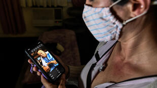 Ariane Gutierrez looks at a cellphone photo of her father Gerardo Gutierrez, who died of Covid-19 on April 28, 2020, in Miami Beach; the Florida supermarket where he worked would not allow employees to wear masks