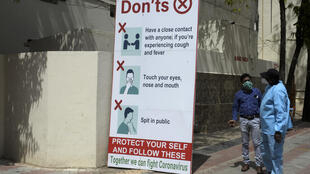 People wearing personal protective equipment (PPE) stand beside a notice advising guidelines to prevent the spread of the coronavirus at the entrance to a church before a Sunday service in Hyderabad, India on July 19, 2020.