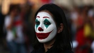 Una mujer libanesa pintada como el villano del cómic 'The Joker' durante una manifestación en Beirut, el 19 de octubre de 2019.