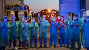 Parte del personal sanitario del hospital general de Burgos devuelve los aplausos a su labor de la ciudadanía a las puertas del centro, el 25 de marzo de 2020 en esa ciudad al norte de España