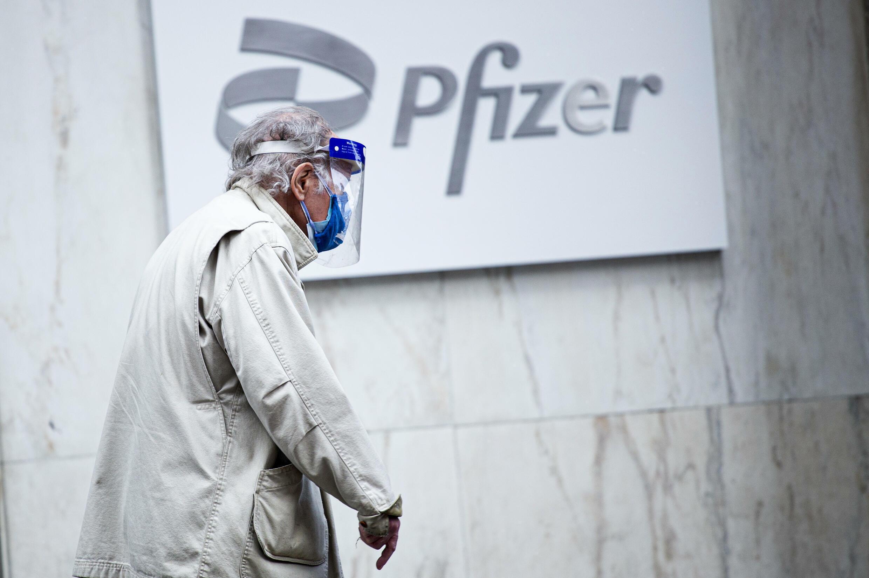 رجل يمر أمام مقر شركة فايزر في نيويورك واضعا كمامة وقناعا واقيا، في 11 آذار/مارس 2021