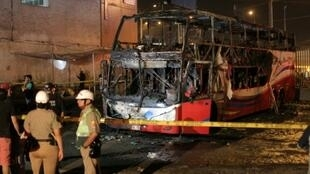Police stand around the charred remains of a bus that caught fire in Lima killing 20 people