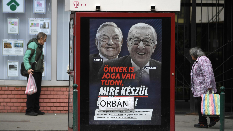 """El cartel que generó polémica, representando a los retratos de ean-Claude Juncker (der.) y  George Soros, con el eslogan """"Usted también tiene derecho a saber lo que está preparando Bruselas"""" con """"Bruselas"""" cubierto por """"Orbán"""", en Budapest, el 26 de febrero de 2019."""