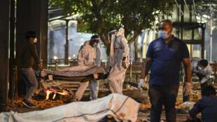 Des proches et du personnel soignant transportent vers un crematorium le corps d'une personne décédée du Covid-19, à New Delhi (Inde) le 22 avril 2021