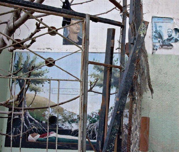 """Légende (extrait) : """"Mémorial du martyr Hamouda Chtewei aménagé devant la maison familiale. Au mur, une peinture du martyr, enveloppé des couleurs palestiniennes, dans sa tombe, sur laquelle poussent des oliviers ; au-dessus, un portrait de lui."""""""
