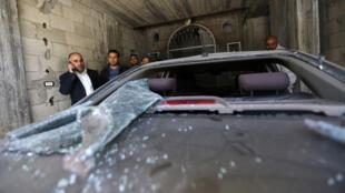Fayez Abu Eitta, un membre du Fatah (à gauche), inspecte sa voiture endommagée, le 7 novembre 2014.