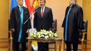 Mohamed Morsi (c) takes the presidential oath of office in 2012