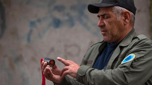 A man holds a unit of a cluster munition in the breakaway Nagorno-Karabakh region's main city of Stepanakert