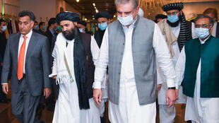 Pakistan's Foreign Minister Shah Mehmood Qureshi (third right) walks with Taliban co-founder Mullah Abdul Ghani Baradar (second left) ahead of talks in Islamabad intended to push for peace talks