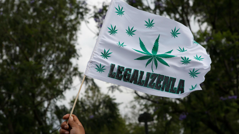 """Un participante sostiene una bandera durante una marcha por las calles en apoyo de la legalización de la marihuana en la Ciudad de México, México, el 5 de mayo de 2018. Las palabras en la bandera dicen """"legalicenla"""""""