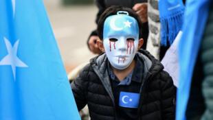 Un garçon portant un masque à une marche de protestation des Ouïghours à Bruxelles, le 27 avril 2018.